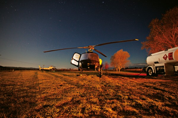 Helicopters, the ultimate piece of farm machinery, play a crucial role in protecting crops from frost. Fueling up at 3 am in Rangiora, Rob Kitow is one of the first in the field in the modern 24-hour farm, followed closely by the dairyman.