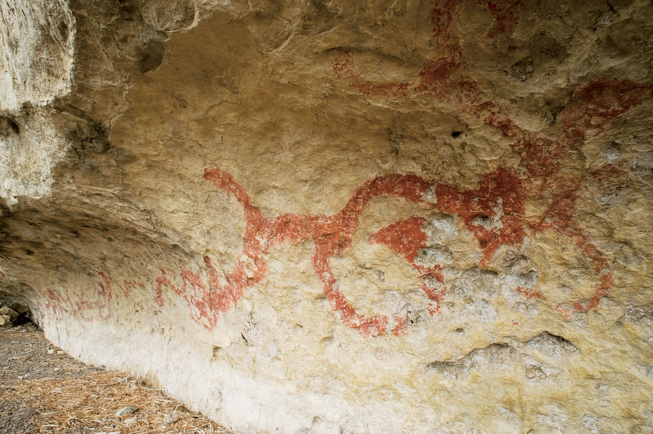 Perhaps the best-known Maori rock art site in the South Island, the vivid red images at Takiroa, near Duntroon, reveal a range of different techniques and images, most notably the long horizontal reptilian figure in the main shelter. Drawn, painted or scratched in a scraffito-like process, identifiable forms include European-style sailing vessels and horses as well as taniwha, birds and other animals. In 1916 several pieces of marked rock were removed and are now housed in museums around the country.