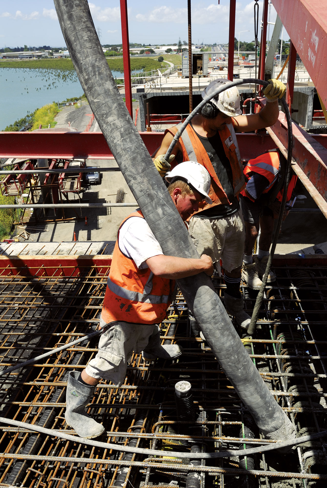 Dan Noble and Johny Hope pour concrete on Pier 2 of the Manukau Harbour Crossing. When completed, the bridge will contain around 26,000 tonnes of concrete and 1000 tonnes of steel on foundations that have been engineered to carry up to 500 vehicles at any one time—as well as the possibility of a future low-level rail.