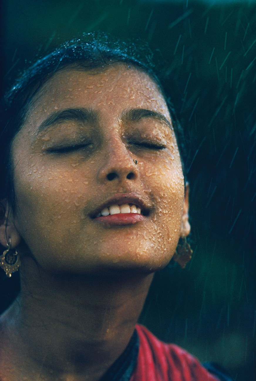 """Evoking the eroticism of the monsoon—a common theme in Indian literature—a beautiful peasant girl lifts her face to the rain. This portrayal of the monsoon was a hit with every magazine that ran Brake's 1960 """"Monsoon"""" photo-essay, but the composed nature of the shot later became controversial. A young actress, Aparna Das Gupta, was posed to Brake's designs beneath a watering can."""