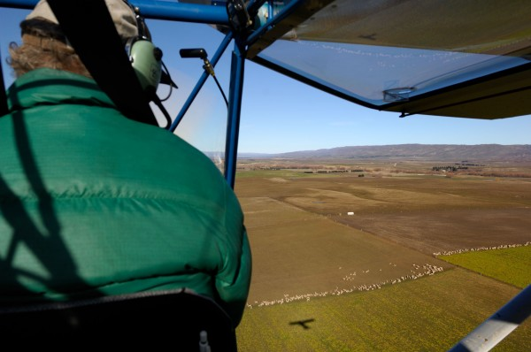 At the controls of his RANS S7 Courier, Dave Witherow contemplates the shadow of his microlight moving over the austere landforms of Central Otago near Ranfurly.