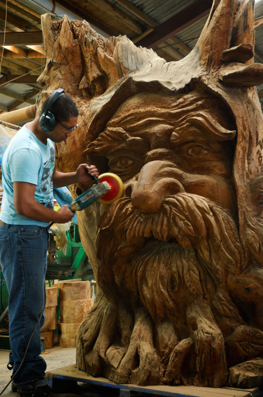 At Ancient Kauri Kingdom in Awanui, tree spirits are released from swamp kauri by way of sensitive chainsaw surgery by Warwick Lilley—here Joe Waru applies the final polish. The long gone kauri forests of Northland provide employment for locals.