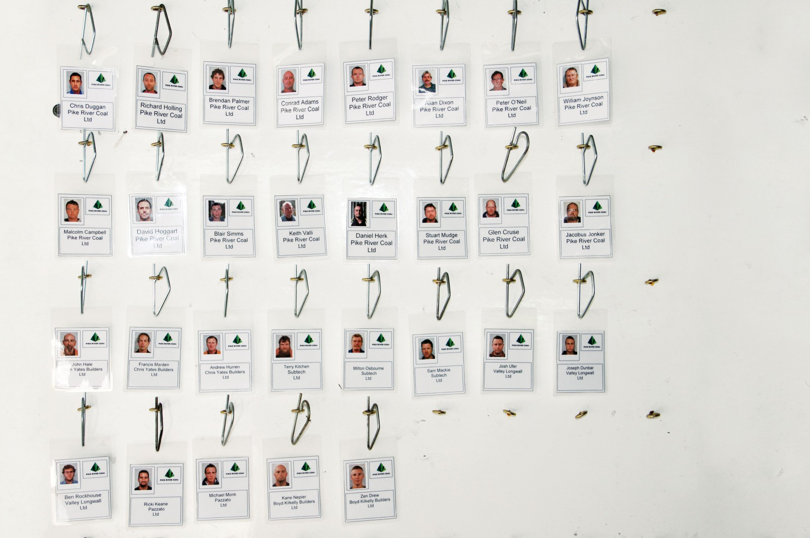 Faces of the 29 men trapped in the Pike River Coal Mine stare from a tag board—a system used to keep track of who is underground at any given time.
