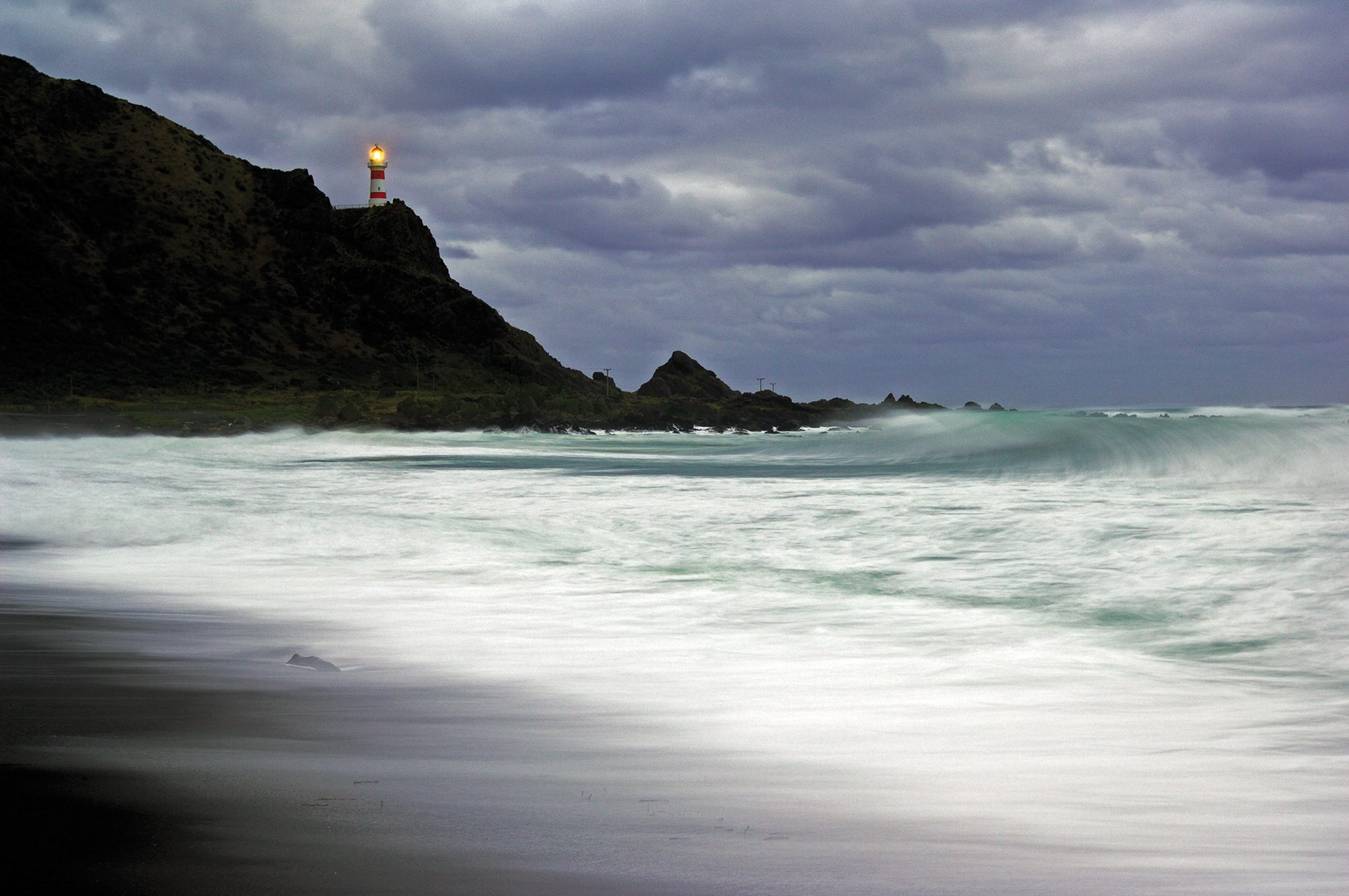 Casting a frail loom during a storm, Cape Palliser lighthouse marks the southern-most tip of the North Island. Built in 1897, the light has been managed from a control room in Wellington since 1986.