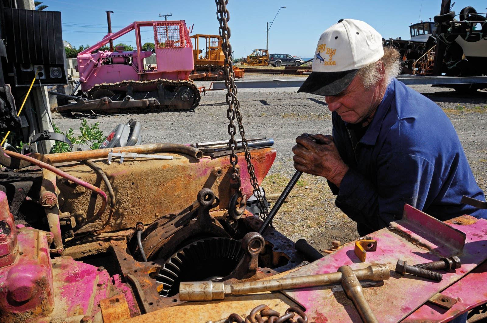 "Known locally as ""Curla"", fisherman and mechanic Evan Gray makes some running repairs to the steering mechanism of his aging bulldozer ""Tinki Winki"". Though old age and corrosion seems to take its toll on everything (and everyone) in Ngawi, ingenuity and treachery prevail."