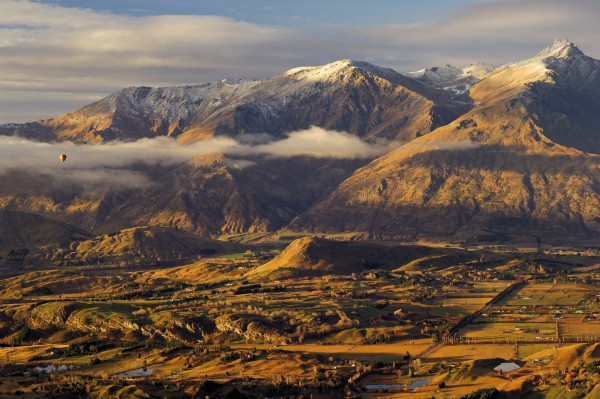 A hot air balloon lifts off from the base of The Remarkables at first light. The spectacular range, which dominates almost every view from the town—topped by Double Cone (2324 m), at right—has been uplifted along a fault line and made steeper by glacial action. The valley to the left of the peak is the site of Queentown's second ski area—known locally as 'The Remarks'—considered a family alternative to Coronet Peak, from which this frame was shot.