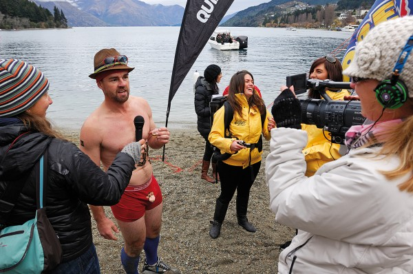 A participant in the 'Hundy 500' (top) is interviewed following one of the Winter Festival's more onerous events—running an obstacle course (including water features) in mid-winter wearing nothing but briefs. Seeking more comfortable climes (bottom), patrons gather in a warm corner at the Cowboy Bar, one of Queenstown's many restaurants and bars sporting open fireplaces.