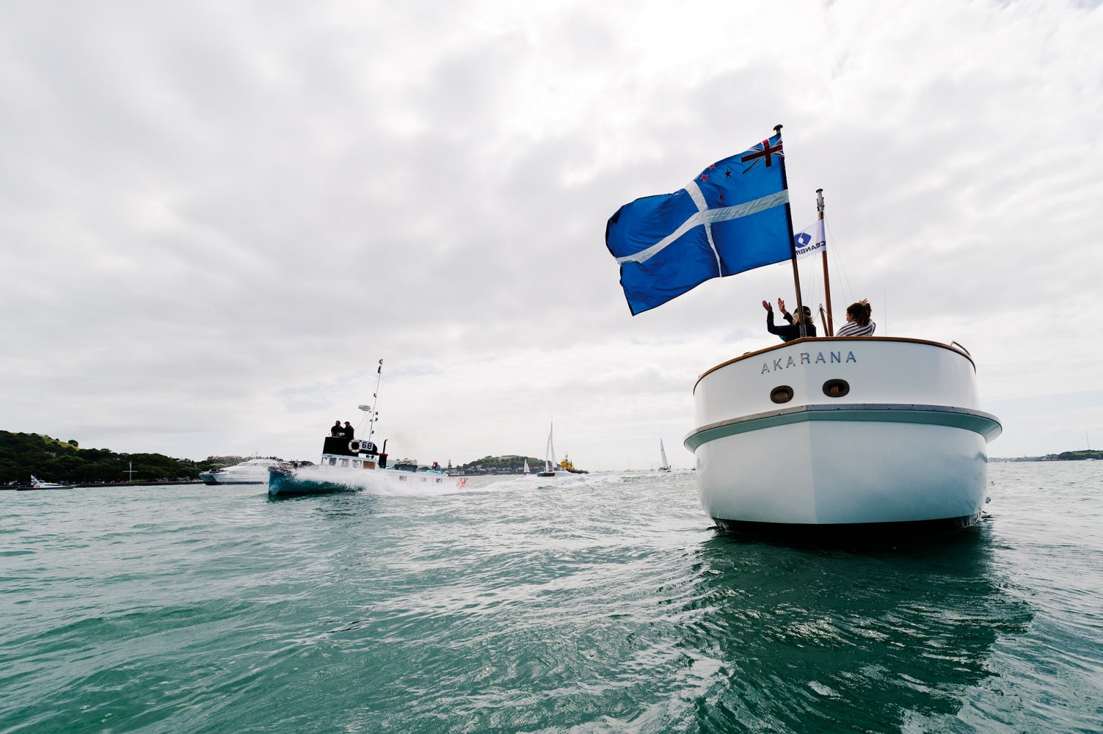 """A new ingredient in the Auckland Anniversary Day Regatta is a tug boat race—although strictly speaking it is a """"workboat"""" race. It pays tribute to the huge contribution power-driven vessels have made in the development and commerce of Auckland and the dozens of ports around our coasts—not only tugboats, but fishing boats, pilot launches, passenger and trading launches. Observing the race is the restored Auckland Harbour Board pilot launch Akarana from 1950."""