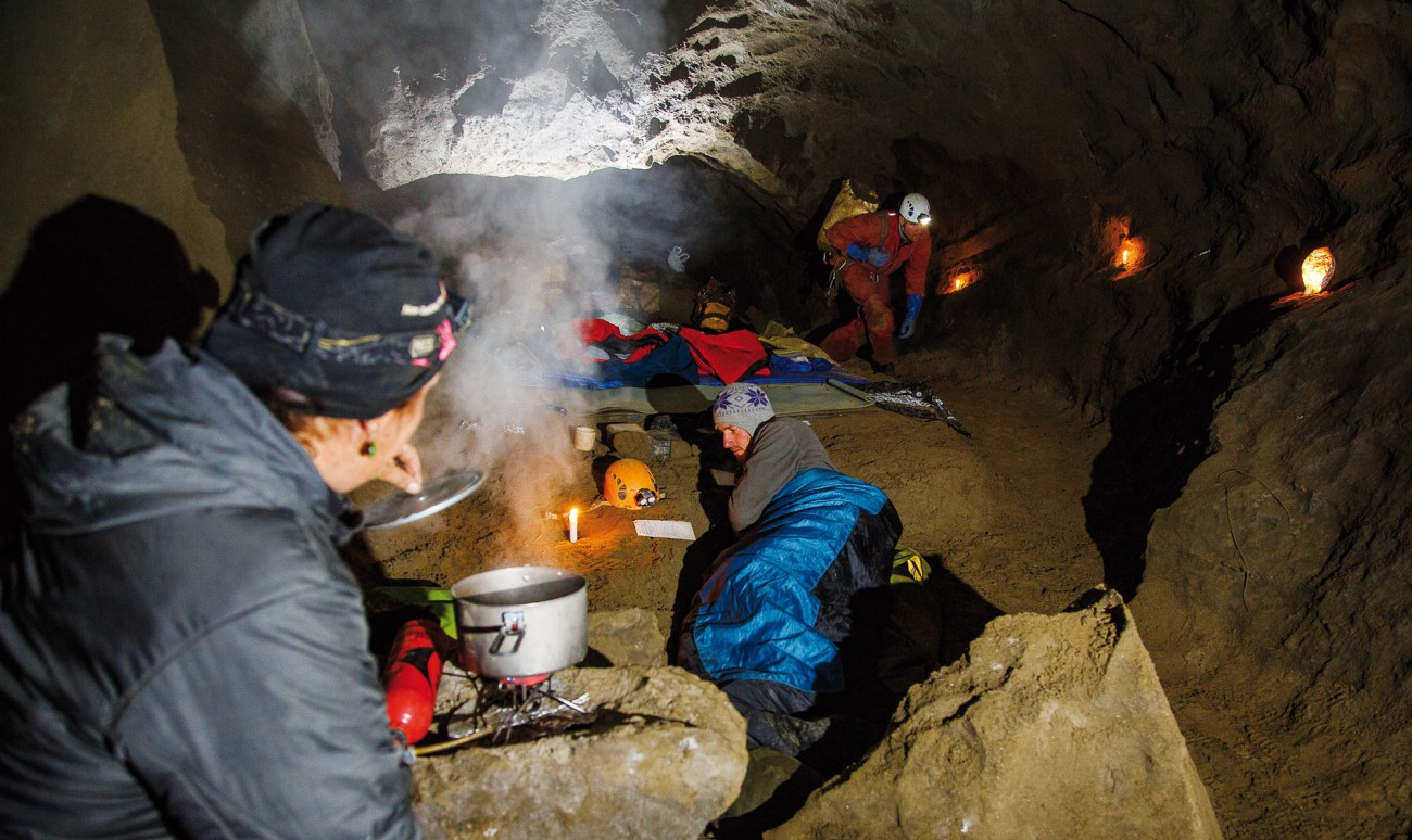 The Chocolate Room is one of those rare spaces in a cave system that is elevated, dry, level and relatively warm. The living room-sized space, 500 metres underground, has been the headquarters of every expedition into Stormy Pot, and a cherished home away from home for the caver for weeks at a time. Here Heidi Godfrey keeps the home fires burning as Kieran Mckay reviews his growing map of the system and Chris Whitehouse prepares to head out to the end of the cave.