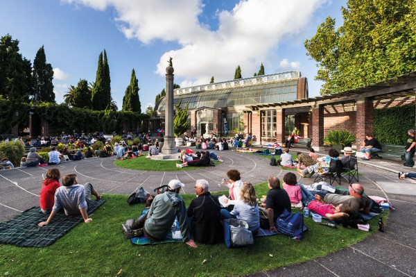 Concert-goers relax in the courtyard of the Winter Gardens during a Music in Parks performance by New Zealand singer-songwriter Miriam Clancy. The beautiful cool house (a twin structure of the tropical house on the same site) was designed by renowned Auckland architect William Gummer, who commissioned sculptor Richard Gross's beloved leaping cat statue atop the central pillar.