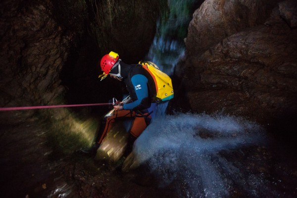 Alain Rohr abseils toward the end of the canyon at Mathers Creek, Haast, in fading light. While canyoners always plan to exit in daylight, first descents in particular can involve long, draining days if delayed by unexpected features.