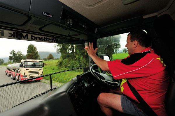 Westland Milk tanker driver Chris Roberts, left, gives a collegial wave to another of the company's 23 vehicles on the road, collecting 'white gold' from farms around the Kowhitirangi district.