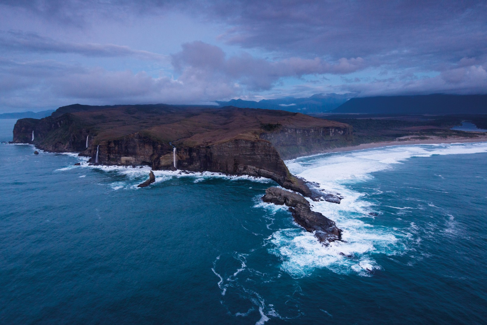 With nowhere left to flow, the brimming Dougal, Donald, Duncan and Whiskey Creeks plummet over Cascade Point into the sea south of Jackson Bay, their names recalling the Shetland Islanders who came here seeking gold in 1860.
