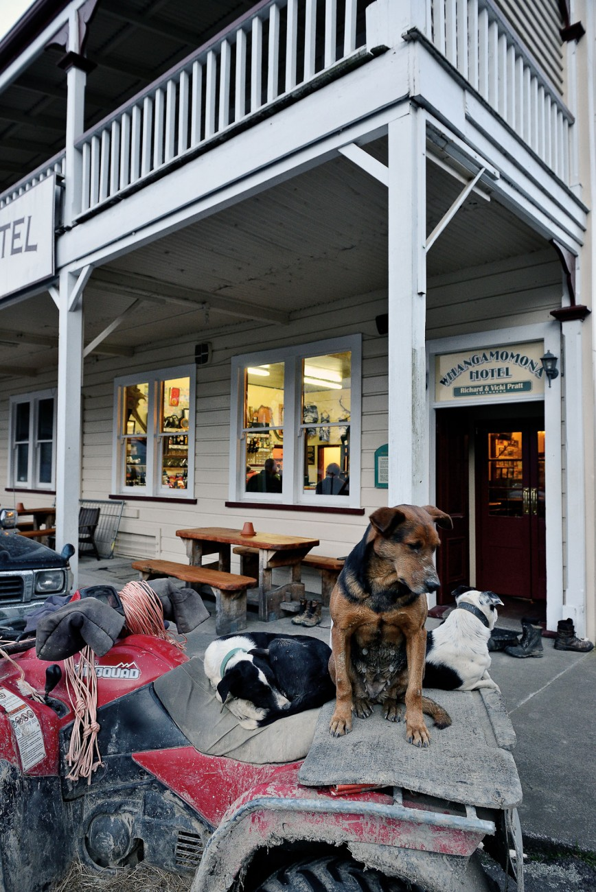 "Fifteen kilometres up the road, locals enjoy a Friday night at Whangamomona Hotel. Muddy boots and dogs stay outside. Farmer John Herlihy has his working dogs well trained: ""They know I won't be long."""