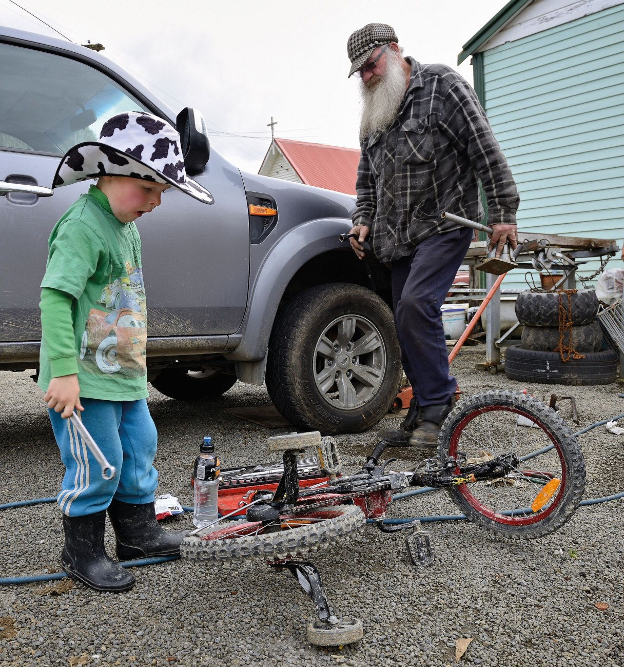 The current president of the Republic of Whangamomona, Murt Kennard, operates the only garage on the Forgotten World Highway. He fixes anything that breaks in the district, including the wheel bearings of this truck. His four-year-old neighbour, Gus Hutchinson, uses the opportunity to effect some repairs on his vehicle too.