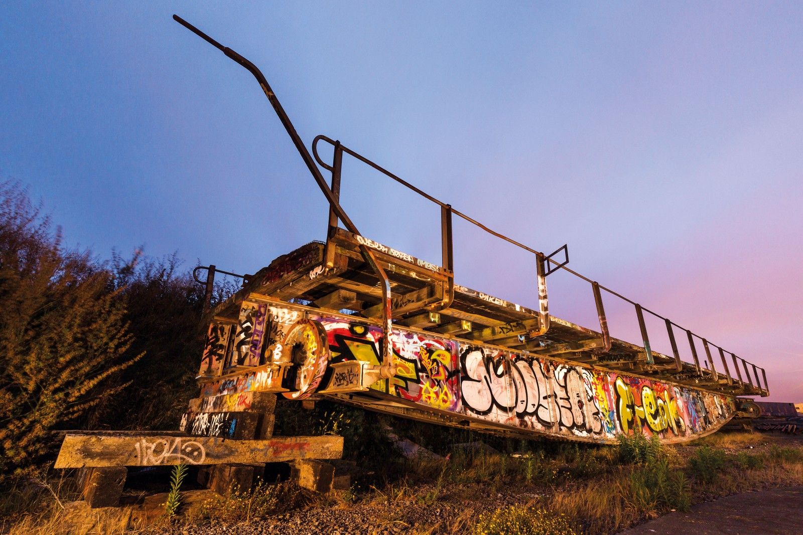 Decades of tags, including that of Wongi Wilson—going by his street pseudonym 'Freak'—adds several layers of paint to the rusting hulk of a retired railway turntable in the railyards in Waltham, Christchurch. Like others, Wilson has since graduated from tags to street art, which ironically owes its legitimacy to the movement of illegal graffiti.