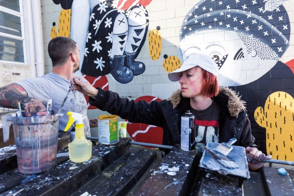 In Auckland, street artist and tattooist Tom 'TomTom' McMillan works on a piece made in collaboration with multimedia artist Misery (Tanja Jade), one of five murals painted by nine artists over two days as part of the second Bradley Lane Mural Project in Glen Innes.