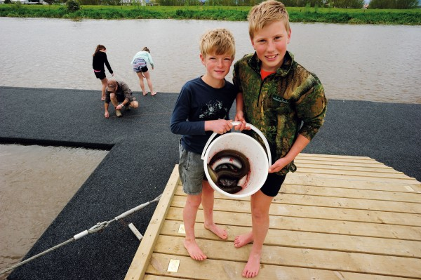 Showing off the afternoon's catch, school children use a newly installed floating pontoon on the banks of the Piako River to catch eels. In 2007, a group of Ngatea School students concerned about pollution in the Piako made a short film about the river and restoration efforts, which took top prize in the international Panasonic Kid Witness News competition.