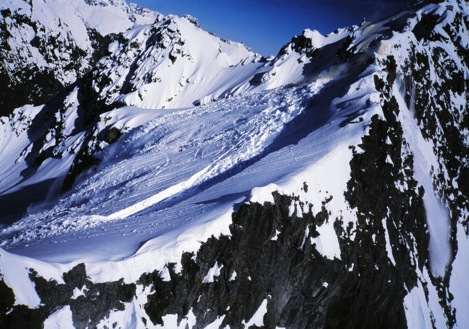 "In the main image, smoke from a detonated ""bomb"" (visible at top right) and an ominous crack indicate that this snowfield has been given a nudge and is about to take off down the mountain."