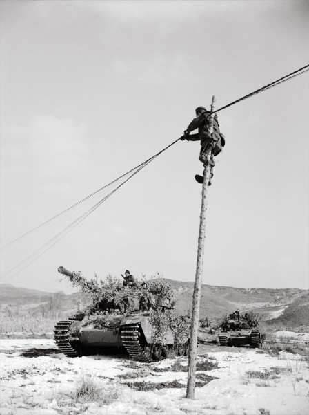 A New Zealand linesman raises telegraph wires to give clearance for British Centurion tanks. Erecting the poles in frozen winter ground was made easier by pouring petrol into a depression and igniting it.