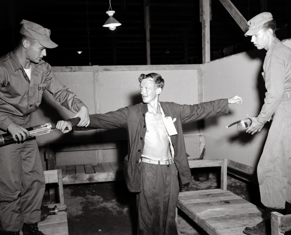 "Gunner Graham Garland (here being dosed with anti-lice spray upon his return from North Korean captivity) was Kayforce's only prisoner of war. He was captured while on observation duties with a British unit in November 1951, and held for 20 months, fed on two cups of rice a day and a ""charred barley"" drink for lunch. Although the West accused the communists of brainwashing and forced ""re-education,"" more prisoners died while being held by UN forces than by the communists."