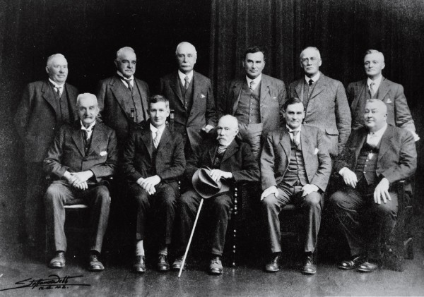 "Ell's schemes always outstripped his means—a situation which drove to distraction the many fund-raising bodies he formed to finance construction of the Summit Road and its amenities. The Summit Road Scenic Reserves Board, (Ell is seated fourth from left) was not alone in threatening legal action against him to recover money spent without its authorisation. Ell preferred the work site to the board room, getting his hands dirty and putting such workers as he could call upon to good use. The dole queues of the Great Depression proved a plentiful source of cheap labour—artisans and labourers soon teasingly dubbed ""Ell's angels"" (below)."