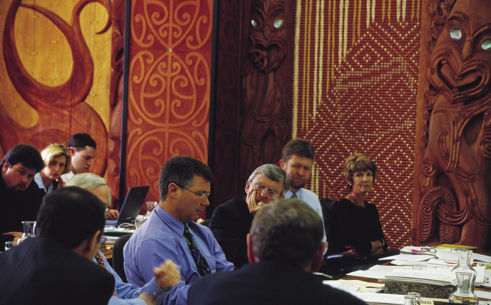 Under the inscrutable gaze of ancestors, representatives of the Public Trust Office are questioned during a select-committee hearing in the Maori Affairs Select Committee Room, named Maui Tikitiki a Taranga. While the common perception of Parliament is of rhetorical cut-and-thrust in the debating chamber, the less visible work of select committees is at least as important. The 17 committees, on each of which 8–10 Members of Parliament serve, examine legislation, review public expenditure, hear petitions, conduct inquiries and more.