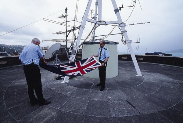 """Pat Magee (left) and Dan Matata fold the flag that flutters by day over the Beehive. To minimise entanglements in the capital's windy conditions, the flag comes in three sizes, known as the """"tablecloth,"""" """"teatowel"""" and """"handkerchief."""" During raising and lowering, protocol dictates that the flag must never touch the ground."""