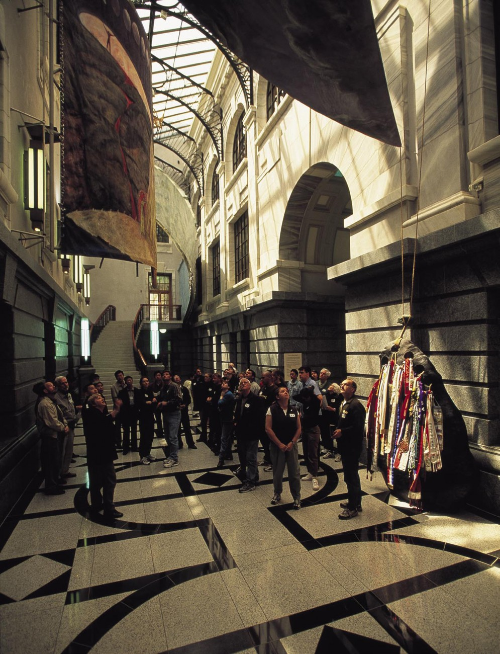 """Visitors crane their necks to take in the wonders of the Galleria, a newly enclosed space in Parliament House containing commissioned artworks, including Richard Parker's ribbon-bedecked """"Mooring Stone."""""""