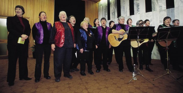 """When the Wellington women's trade union choir—whimsically named Choir Choir Pants on Fire—launched its second CD in Parliament, it enlisted the support of Prime Minister Helen Clark (at far left), who joined in a chorus of """"Build High the Bridge,"""" an American workers' song."""