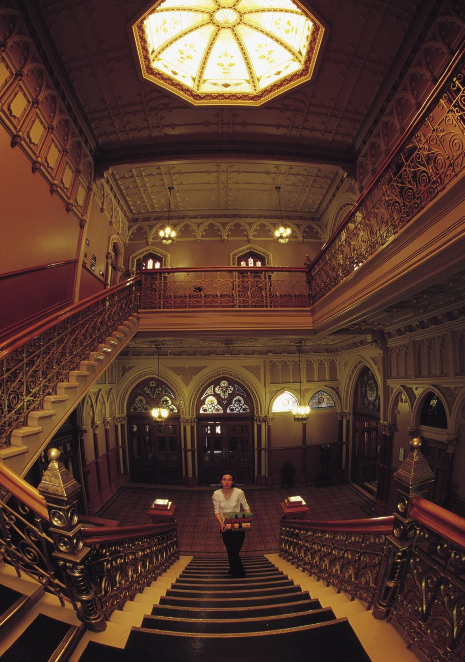 Over half a million books fill the Parliamentary Library, its shelves in part swollen by a legal requirement that one copy of every New Zealand publication be donated to it. The duties of library staff such as Wendy Johnson, here ascending the building's ornate staircase, extend far beyond shelving and issuing books. Staff provide a comprehensive research service to MPs, unearthing quotes and comments and assembling dossiers of information on virtually any subject. Whenever the House is sitting, the library stays open, no matter how late. It is just one of the many services that keep information flowing down the corridors of power.