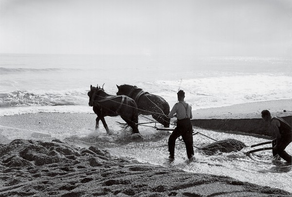 Periodically, the entrance has closed completely, and locals—using a horse-drawn scraper in this 1935 photograph—have struggled to re-open it.