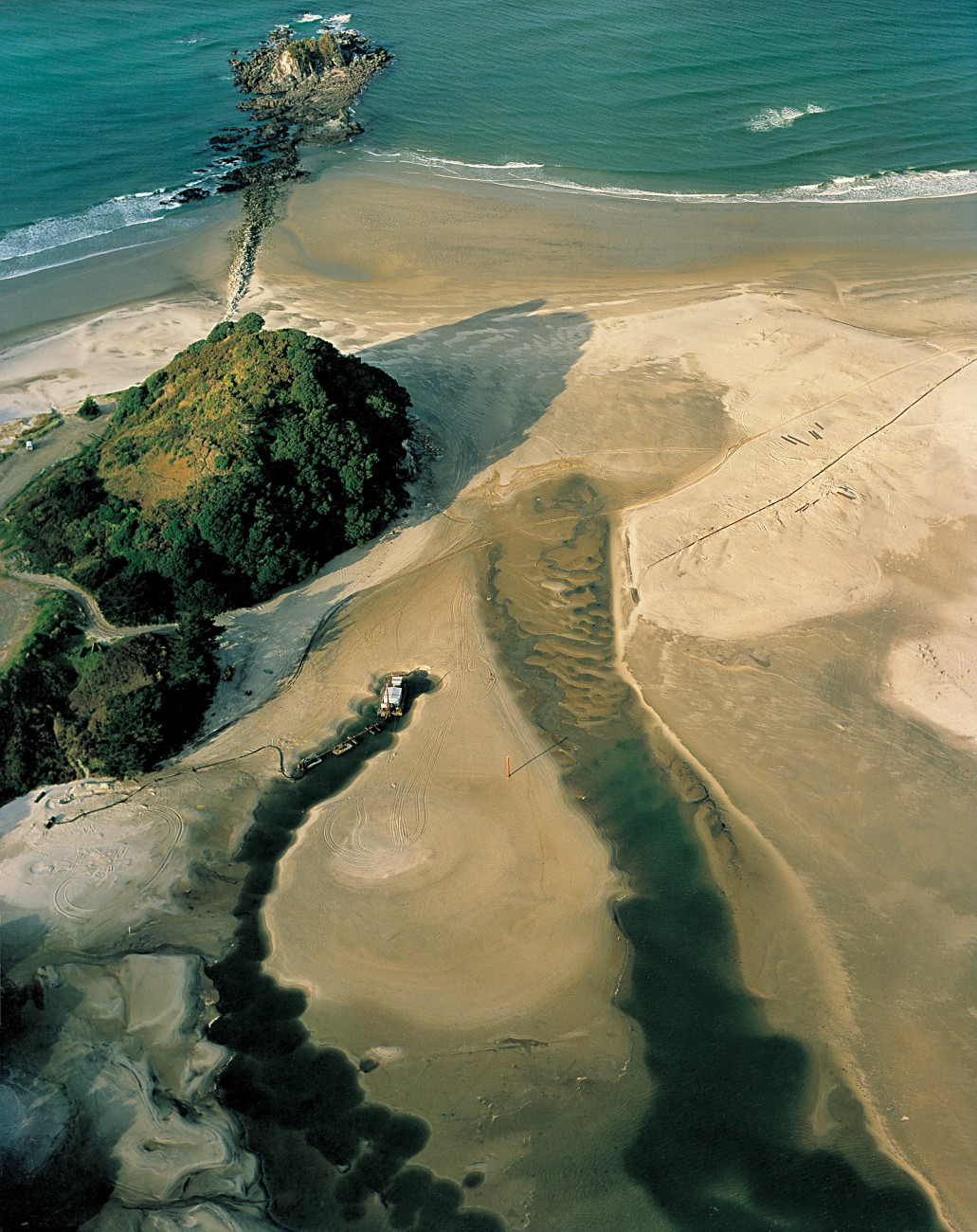 """At Mangawhai, the harbour entrance historically lay beside a bushclad headland, but from the mid-1970s sand started to clog this channel, and a new, unstable entrance formed to the south where the sea had breached sheltering with dozens of pieces of heavy equipment in an operation they dubbed """"the big dig."""" When that effort proved unsuccessful, they used a dredge to wall off the unwanted southern entrance."""