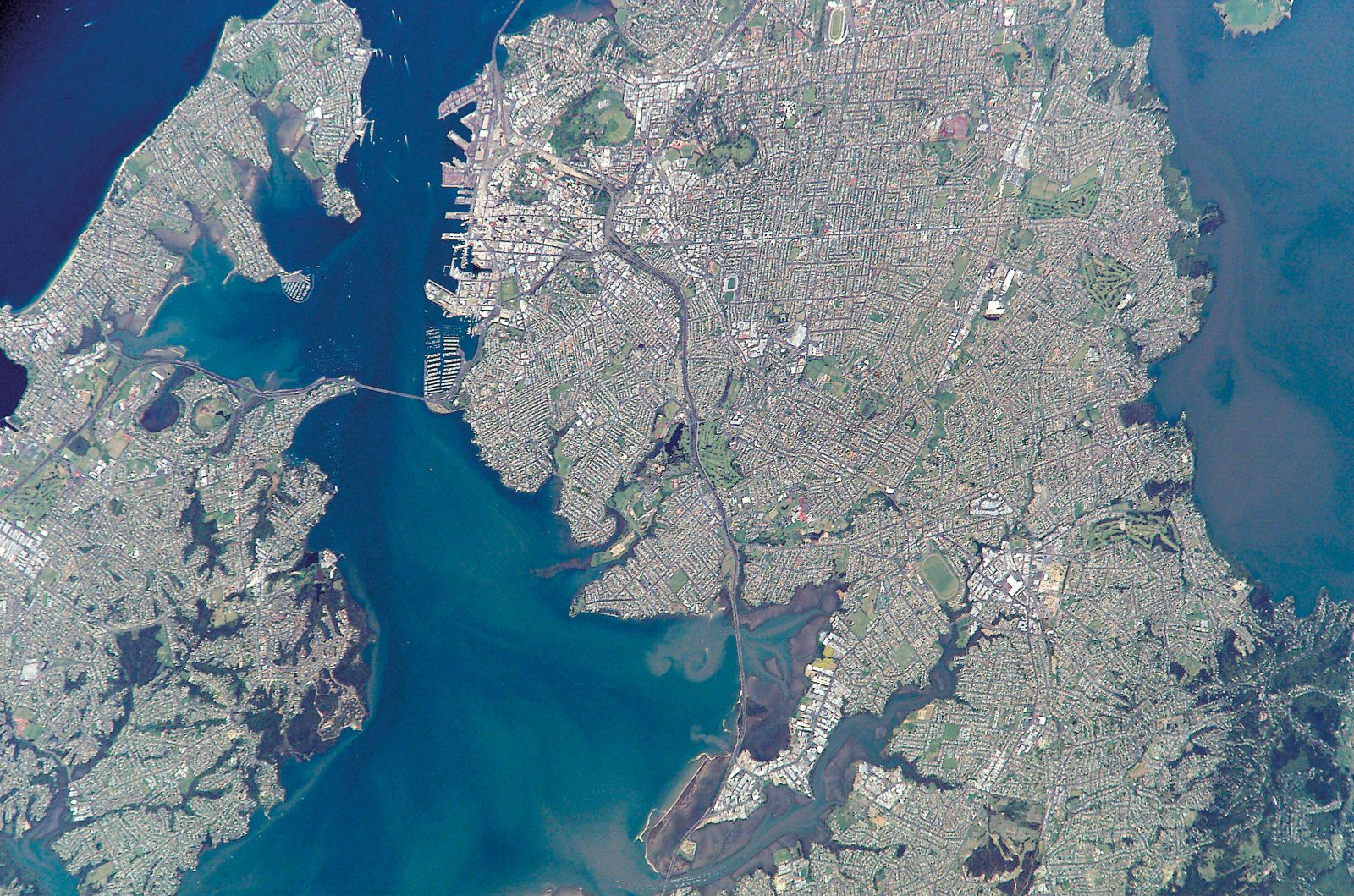 The other a congested metropolis in the north. Downwind of Auckland Island, current eddies can be seen extending east for many kilometres. Auckland city has been photographed with the aid of an 800 mm telephoto lens, which gives a considerable degree of enlargement.
