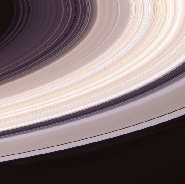 The impressively solid appearance of Saturn's rings is deceptive. About 250,000 km in diameter, they are less than a kilometre thick and contain very little actual material. A shimmering palette of pastel pinks, yellows, browns and greys is captured in this natural colour image (top). The rings are composed mainly of water ice—white in its pure form. Colour variations probably indicate contamination with other materials, such as carbon compounds, while brightness corresponds to concentration of particles. The brightest band, curving from lower left to upper right, is the B ring—third out from the planet. Threadbare rings cross their own shadows and the planet appears blue through the lens of a gap (bottom). Closest to the planet, the D and C rings are only a few metres thick and largely translucent. At the top of this picture, we catch a glimpse of Saturn through the Cassini Division, which separates the B and A rings. The blue tinge is caused by the scattering of unidentified particles at blue wavelengths in the cloud-free upper atmosphere.