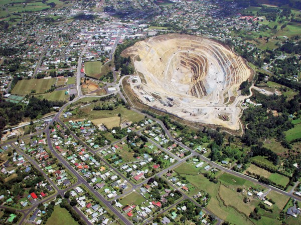 In Waihi, a 250 m deep pit, slated to become a lake eventually, lies within metres of the centre of town, although process- ing and rock disposal take place elsewhere.