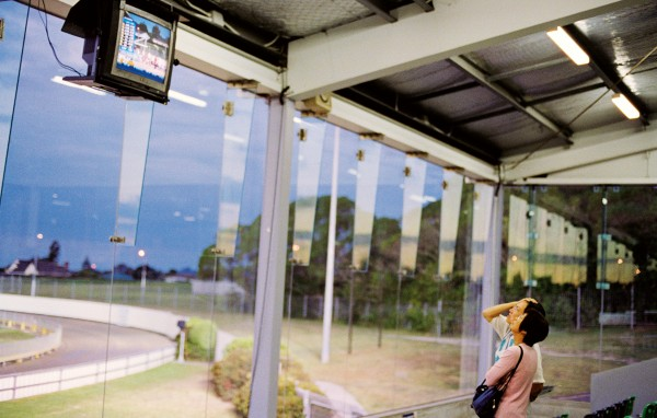 "A couple watch race results on screen at the Manukau track. ""Sprint Club""— with Asian commentaries and hosts—are a recent initiative by GRNZ to boost track attendance at their flagship track."