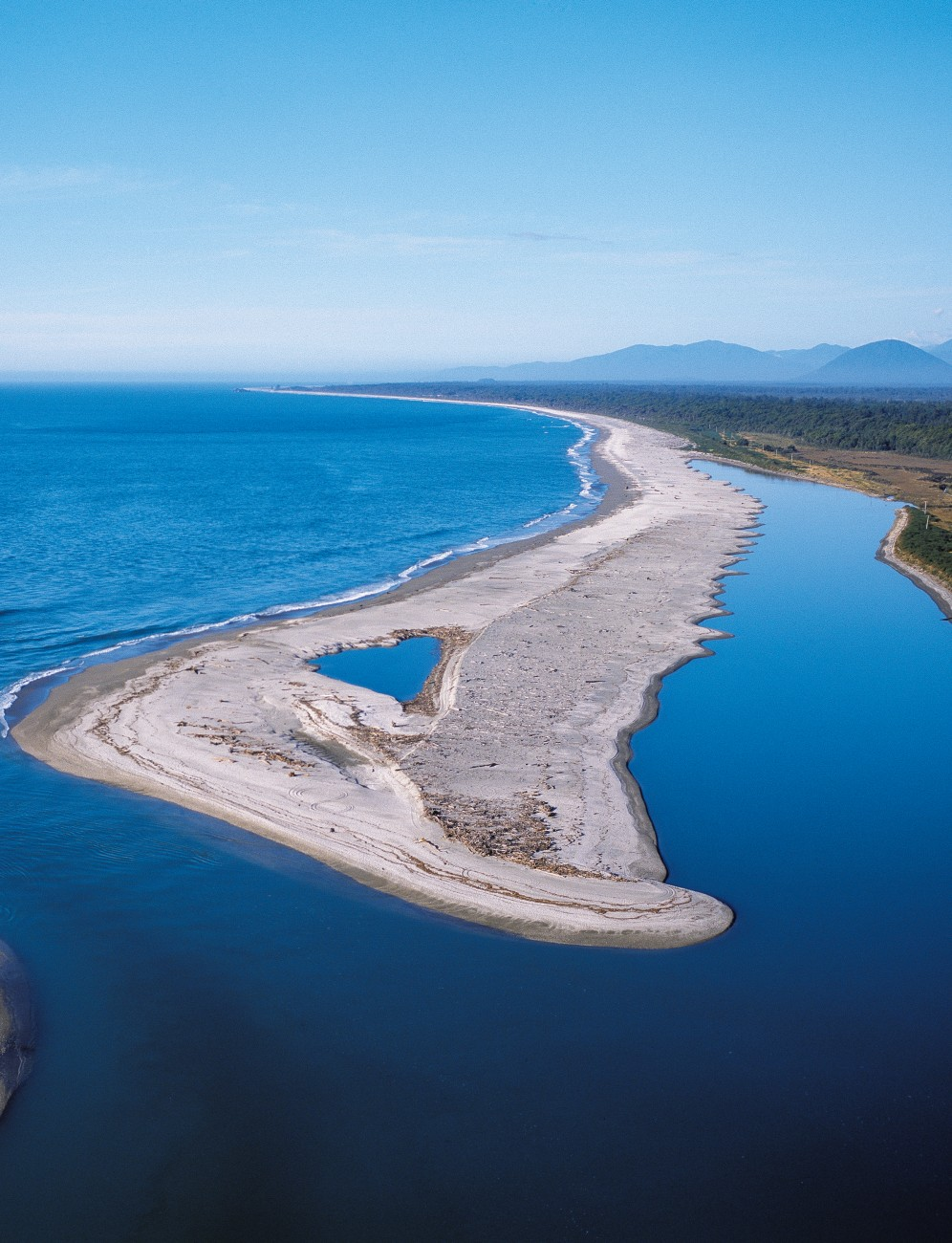 On a calm day the Waiatoto mouth looks benign, but after every large storm, more debris pours into the bay and the configuration of the river entrance may change substantially—just part of the interest in living in a place like Haast.