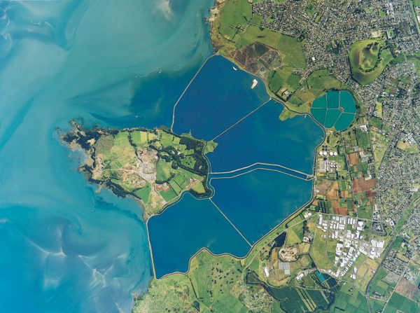 For half a century from the late 1950s, Auckland's sewage was treated in 500 ha of oxidation ponds between Mangere and Puketutu Island (top), but processing has recently been moved ashore and the coast restored to a more natural state (bottom).