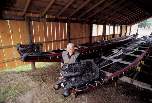 Okains Bay farmer and collector Murray Thacker, with the two largest exhibits in his museum. Most of the collection is housed in the bay's converted cheese factory.