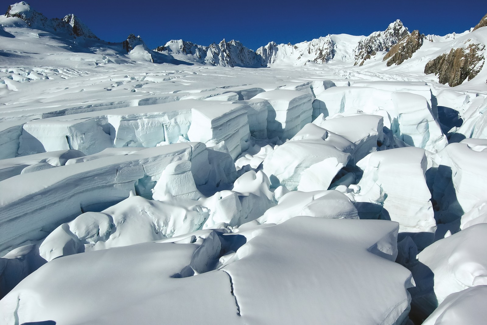 At the top of the glacier, snow and ice accumulate in an icefi eld or nevé. As ice starts to slide down from this area into the glacier, large cracks develop, splitting the frozen mass into vast marshmellowy blocks. Despite the relatively speedy movement of the Fox and Franz Josef glaciers, it will likely be a decade or two before this ice reaches the terminus.
