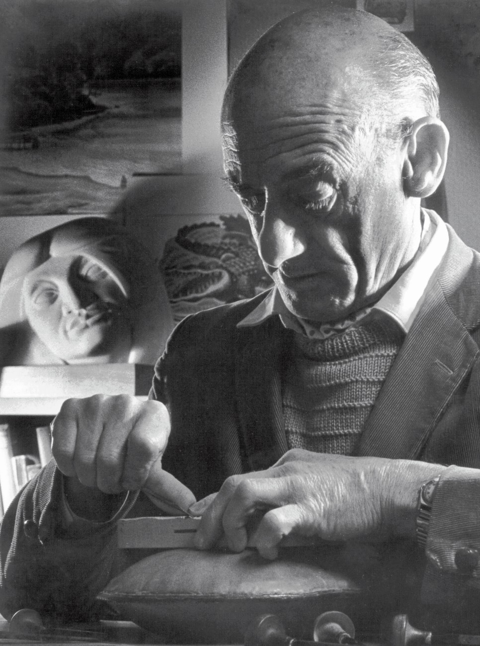 Taylor demonstrates printing from woodcuts (above), cutting a line, laying the paper and peeling off the print. He worked in a converted bedroom in his Karori home—behind him is his first sculpture, Hina, 1957, carved from Mt Somers limestone.