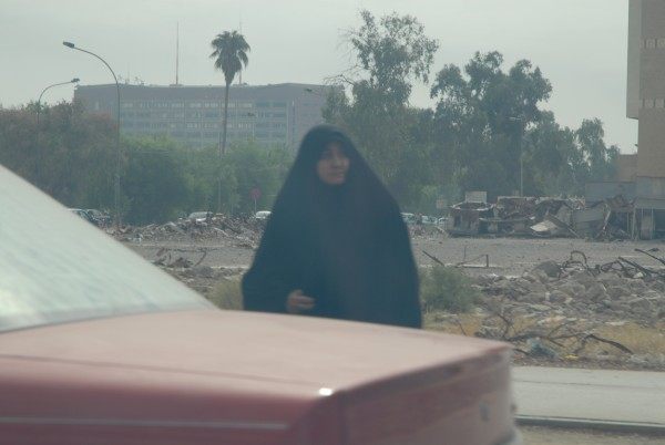 A Muslim woman calmly skirts the wreckage of war as she goes about her daily business.