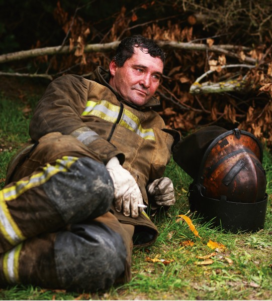 "Exhausted instructor Mike Lennard says that firefighting ""gets in your blood"". His helmet offers a clue to the conditions inside the burning house."
