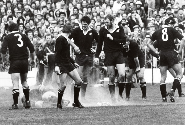 The All Blacks attempt to continue the third test game as a light aeroplane overhead drops flour, pamphlets and stink bombs as a protest against the Springbok tour of NZ.