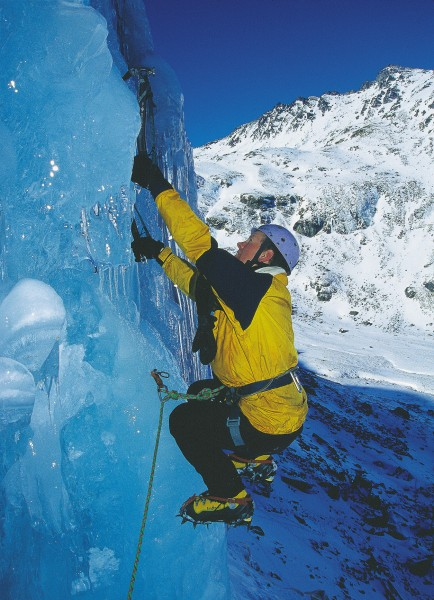 """The author demonstrates a classic ice-climbing position, the """"monkey hang."""" Using crampons, the climber works himself into a crouch. Then, in a sudden movement, stands up to place the ice axe in a new position-typically above an obstacle or patch of bad ice. While in the crouch, the climber's total weight is supported by the arms."""