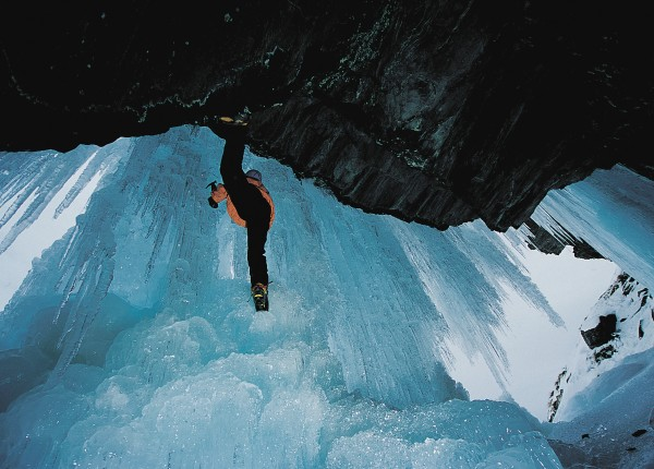Behind an ice curtain, the author gets purchase from a rock overhang to start his climb. He will work his way to the outside of the formation to continue upwards. The glassy look of the ice indicates that it is starting to melt.