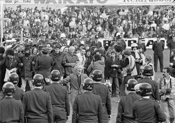 As the on-field group binds in a solid mass at the centre of Rugby Park, Hamilton, on July 25, 1981, the Rev Dr George Armstrong breaks away to address Red Squad police lined up on the northern 22-metre line. Soon after this photo was taken, police pushed Armstrong out through the main exit. Crowds there reached down to rip off his clerical collar, and fists rained on his head.