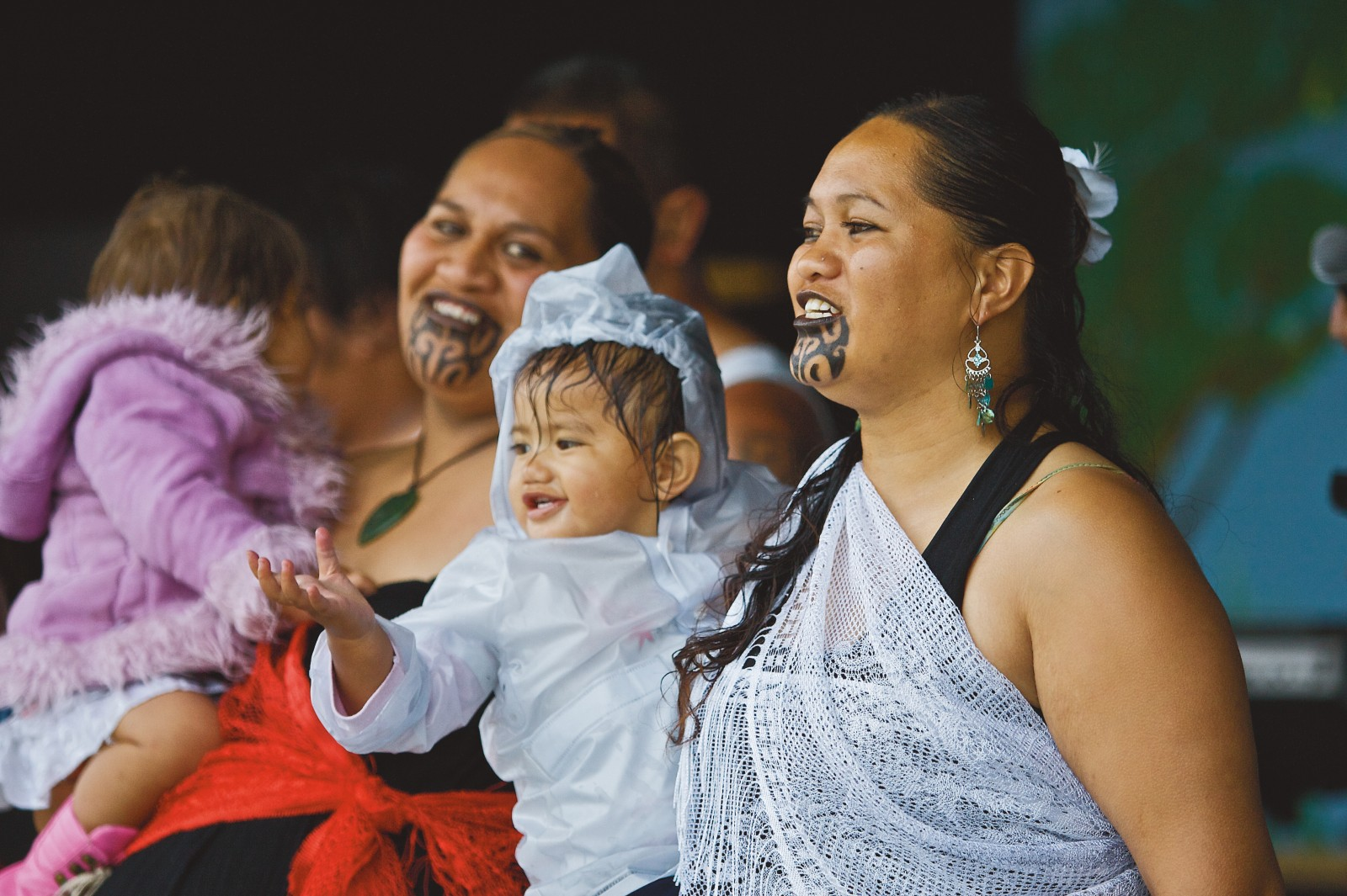 Toddlers join their mothers on stage during a concert, an event that carries on well into the night.