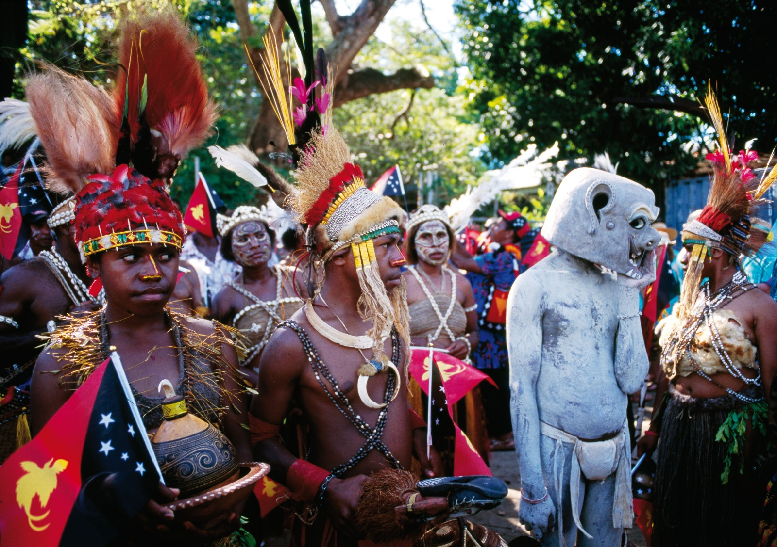 "Dancers gather on the first day of the festival. This troupe, from Goroka in the Eastern Highlands of Papua New Guinea, features resplendent headdresses of bird of paradise feathers that rise and fall in evocative motion during performances. Shells, tusks, gourds and cuscus fur appear as ornaments. The Asaro Mud Man is a legendary figure and popular icon of the festival, disguised with body paint and a large mask made of mud, clay and bark. The figure, said to represent the spirit of a dead person, frightens away potential enemies and carries a whisk to ""shoo away the flies that hover over his rotten flesh""."